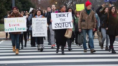 Washington, DC, -- Protesters march in front of the U.S. Department of Justice in response to a grand jury's decision not to indict New York City police officer Daniel Pantaleo for the death of Eric Garner. Garner died on July 17 after being placed in a chokehold while being arrested.