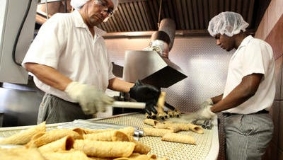 Workers prepare cannoli to be packaged at Artuso Pastry Corp. Jan. 25, 2012 in Mount Vernon. The family business that started in the Bronx in 1946 is expanding by opening a retail store in Mamaroneck and by expanding its bakery to sell wholesale in more supermarkets.