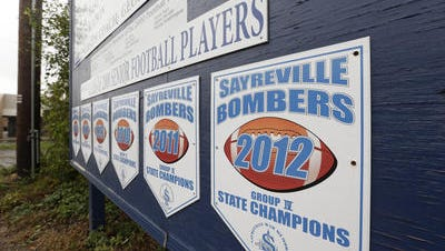 Banners for state championships for the Sayreville War Memorial High School football team are lined up on a sign along Main Street in Sayreville, N.J., on Oct. 11. Seven students were charged with sex crimes in connection with a series of assaults amid an investigation into hazing by the high school football team, which already led to the cancellation of the rest of the season, authorities said.
