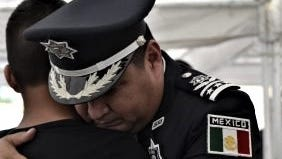A police official gives condolences at the funeral of Officer Manuel Gonzalez Hernandez of the Chihuahua state police, who was killed in an attack Saturday in Cuauhtémoc, west of Chihuahua City.