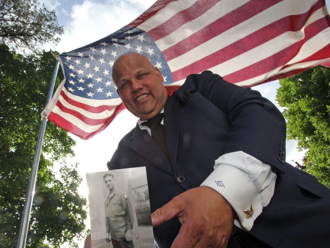 Joseph Jacobino holds the photo of  his father, Leonard Jacobino, a D-Day Veteran outside his childhood home in White Plains on May 29, 2014. Neighbors hung bunting, parked a WWII era jeep in the yard filled with flowers as well as Jacobino's boots he wore when he landed  on Normandy Beach. Leonard Jacobino, of White Plains died on Memorial Day.