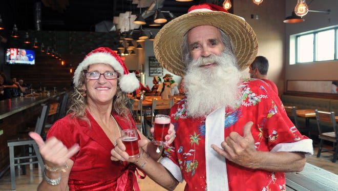 """Terrie and Clifford """"Peanut"""" Kuehner, Mr. and Mrs. Surfing Santa, visited Playalinda Brewing Company's Brix Project in Titusville this week to sample Surfing Santa's Cranberry Ale."""