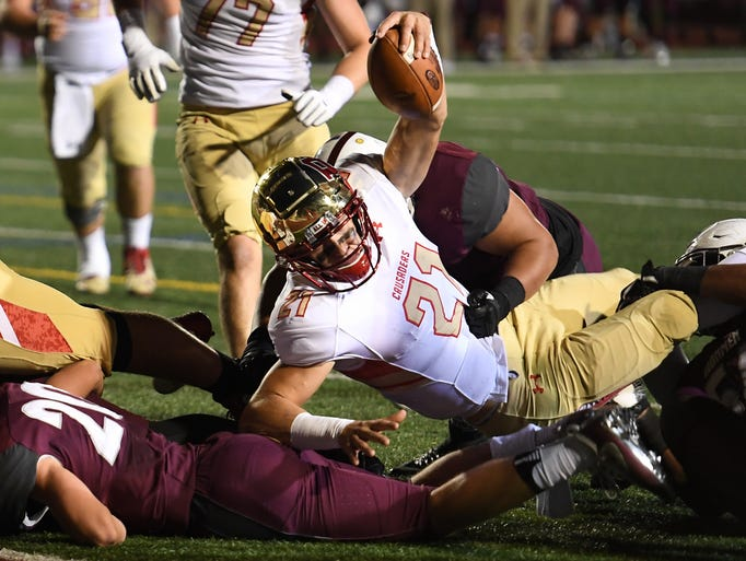 Bergen Catholic's Johnny Langan (21) fights off a tackle