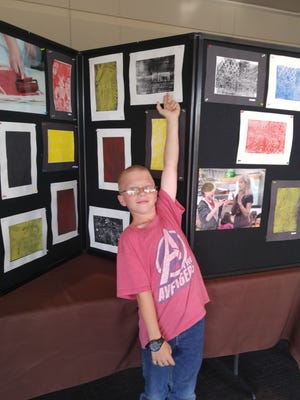 Garret Callahan, a fifth-grader at Red Mountain Elementary School, points to his print during the artists reception at the Kayenta Arts Center in Ivins on April 5, 2018.