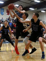 Ankeny Christian seniors Caleb Grizzle and Chad Elrod fight for a rebound with Martensdale-St. Marys sophomore Trey Baker in a Jan. 3 game in Martensdale.