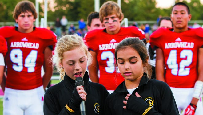 Annie Bartosz (left) of Hartland and her friend Olivia Panos address a full stadium at Arrowhead High School before a 2013 football game. After losing her brother, Jack, to pediatric cancer, Annie created the Gold In September (G9) Childhood Cancer Project, which recently donated $500,000 to Children's Hospital of Wisconsin for cancer research.