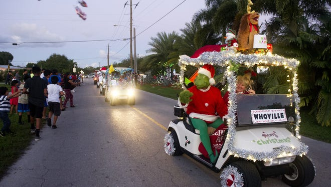 Gord Hobbs and his wife, Jackie, toss candy Saturday during the Indiantown Christmas parade in Indiantown in this file photo from December 12, 2015. The pair, who dressed up as The Grinch and Cindy Lou Who, decked out their golf cart along with other residents of Indianwood Golf & Country Club.