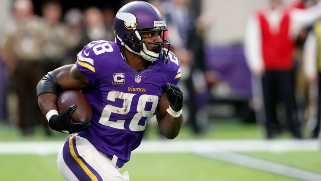 Vikings running back Adrian Peterson runs with the ball.