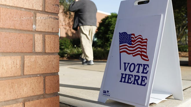 A voter puts on his mask at Gaines Elementary School in Athens on Tuesday.
