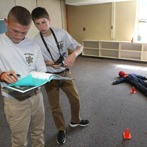 Livingston County Sheriff's Department Explorers Academy students process a mock crime scene at the former Lindbom Elementary School in Brighton.