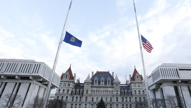 File photo of the state and national flags at half-staff in front of the state capital in Albany.