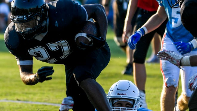 South Side running back Eric Latham (27) is dragged down by a USJ defensive lineman in a TSSAA high school football game between South Side and University School of Jackson (USJ) at University School of Jackson in Jackson, Tenn., Friday, Aug. 3, 2018.