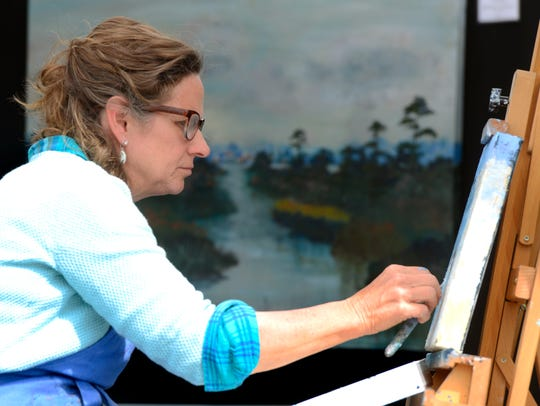 Artist Cheryl Camp works on a painting Sunday during