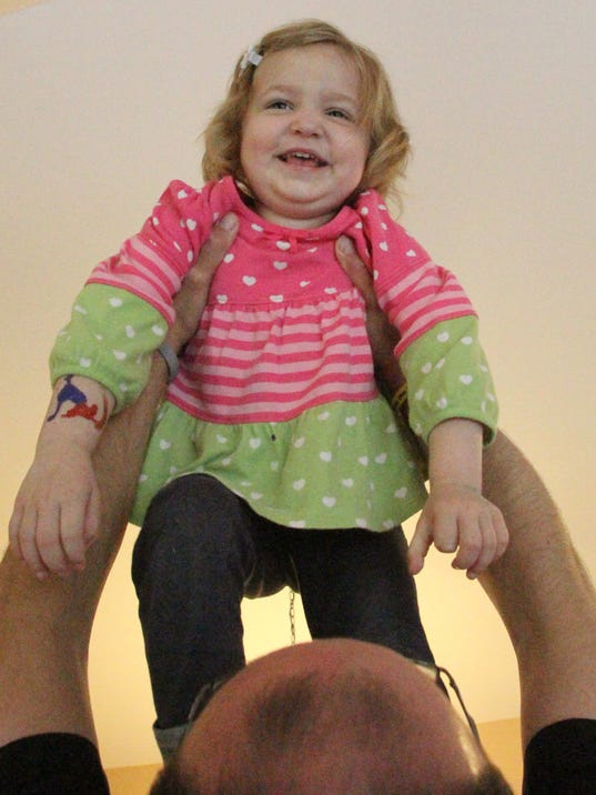 Amelie Strzalkowski giggles and wiggles as her father Jason lifts her high in the family home, Howell Twp. Photo byALAN WARD / DAILY PRESS & ARGUS