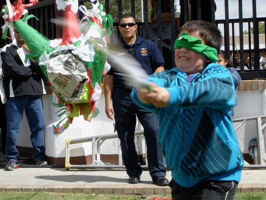 A boy takes a hefty swing at the elusive piñata during
