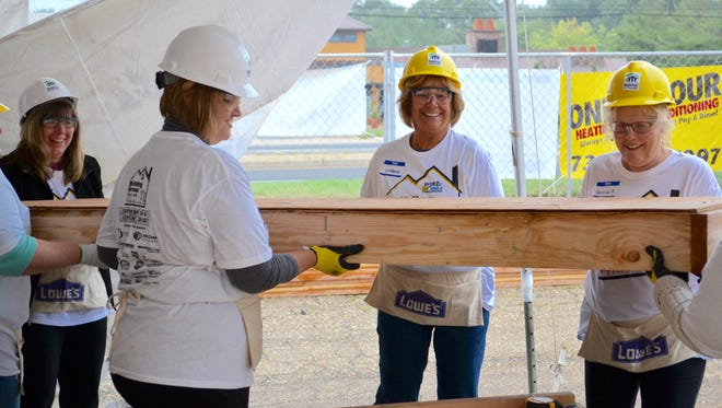 Volunteers from M&T Bank help construct panels at the Building Homes from the Heart blitz build this past October.