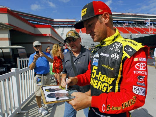 Driver Clint Bowyer signs an autograph before practice for the NASCAR Sprint Cup Series Irwin Tools Night Race on Friday in Bristol, Tenn.