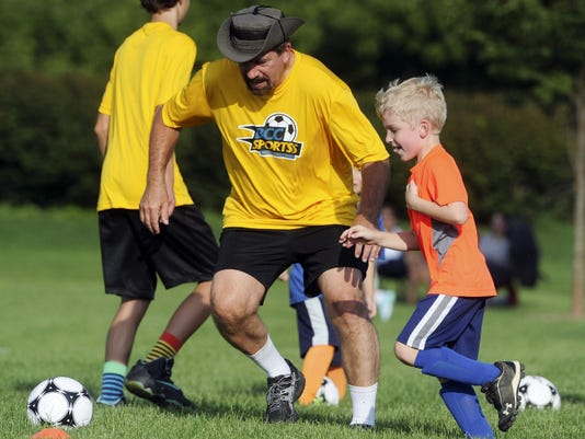 Ron Hill tries to get the ball from 7-year-old Nathaniel Duerr during a drill at Bridgeway Community Church's camp and vacation Bible school.