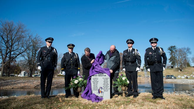 From left to right: officer Kevin Corbin, lieutenant Alan Yeager, Evansville mayor Lloyd Winnecke, Dr. James MacLeod, officer Jay Pagett, and corporal Mike Sides stand as the memorial marker is unveiled during the UE Plane Crash 40th anniversary at Oak Hill Cemetery in Evansville, Ind., on Wednesday, Dec. 13, 2017. Three black ropes were tied around the memorial marker holding the purple cloth to represent the three victims of the crash buried at Oak Hill Cemetery.