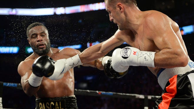 Jean Pascal, left, reacts as Sergey Kovalev lands a punch during their light heavyweight title fight Saturday, Jan. 30, 2016, in Montreal. (Ryan Remiorz/The Canadian Press via AP) ORG XMIT: RYR203