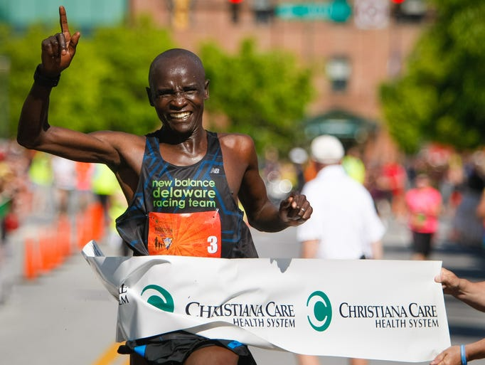 Titus Rotich of Kenya celebrates as he wins the marathon with a time of 2:21:37.  Thousands gather for the 11th annual Delaware Marathon Running Festival at Tubman Garrett Riverfront Park Sunday, May 11, 2014.