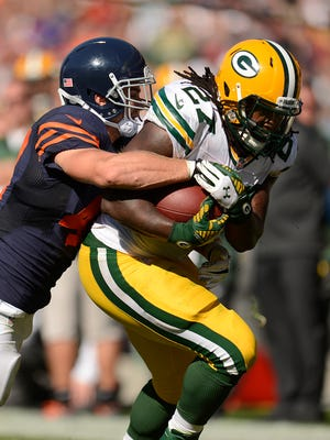 Green Bay Packers running back Eddie Lacy (27) tries to fight off Chicago Bears safety Chris Conte (47) .