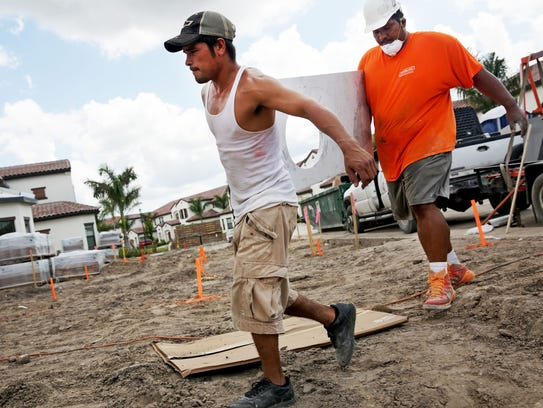 Construction workers Victor Flores, left, and Juan