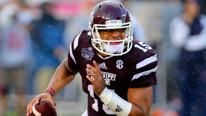 Mississippi State Bulldogs quarterback Dak Prescott (15) carries the ball up the field during the game against the Auburn Tigers at Davis Wade Stadium.