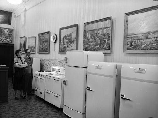 "Ruth Shook and John Medley admire artist George Hamar's art display at the Gas and Electric Appliance Company. (Painting titles right-foreground to left) ""Hunting Scene,"" ""Sorghum Mill Near Nixa,"" ""Ozarks Sawmill,"" ""Tree Cutting in the Ozarks,"" ""Small Town Street Scene,"" ""Butchering in the Ozarks,"" and  ""Bench Show for Fox Hounds."""