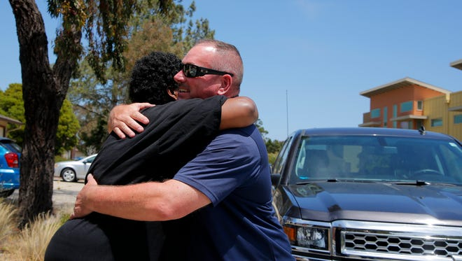 Yolanda Harraway embraces Salinas Police Cmdr. Dave Crabill as he comes to visit her at her new home.