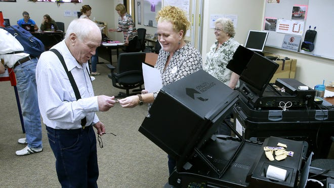 Weldon Queen, left, gets a sticker from Election Clerk Brandy Jordan after voting in June at the San Juan County Fire Operations Center in Aztec.