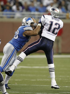 Detroit Lions Ndamukong Suh gives a hard shove to New England Patriots quaterbck Tom Brady after he got rid of the ball without a penalty in the 1st half  in the pre season in Detroit on Saturday, August  27,  2011.