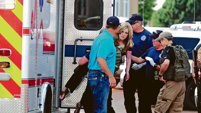 In this Aug. 28, 2017, file photo, an injured woman is carried to an ambulance in Clovis, N.M., as authorities respond to reports of a shooting inside a public library. The shooting left two people dead and four others seriously wounded. A 16-year-old suspect has pleaded not guilty to murder and other charges and authorities expect the case to take much time given the amount of evidence and the number of witnesses.