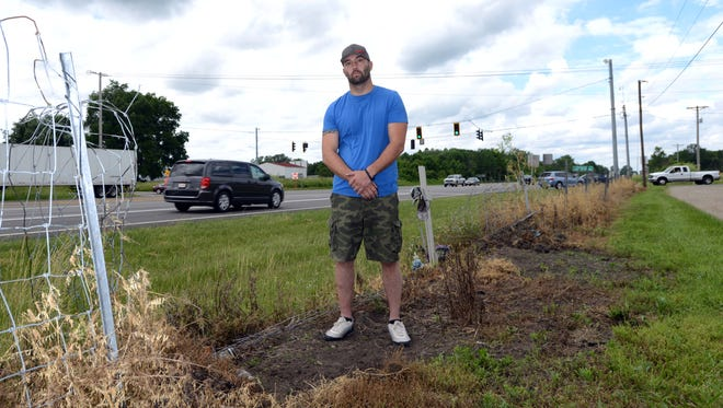 Lyle Campbell stands near the intersection of U.S. 33 and Pickerington Road Wednesday, May 30, 2018. Two years ago while still a Fairfield County Sheriff's Deputy Campbell was struck by a car at the intersection while investigating a crash. Campbell hasn't been able to return to work since the crash and received an involuntary medical separation from the department earlier this year.A cross for Bill Allman, who was also struck in the crash and later died from his injuries, is behind Campbell.