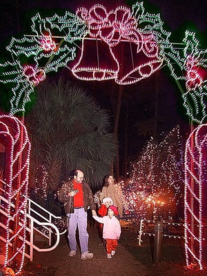 """The Orozco family walks through an electrical candy cane display at Dorothy B. Oven Park's during the City of Tallahassee's """"Elf Night."""" The park used over 200,000 lights for the show."""
