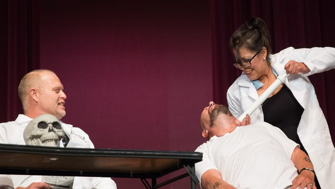 """Corina Preciado, right, acting as a nurse in the New Mexico Behavioral Health Institute, injects a sedative into JR Holton, center, acting as a patient at the institute, during a performance of """"Labels"""" on Friday, Dec. 16, 2016, at Alma d'Arte Charter School. Ernest Ramey, left, plays a doctor in the skit. The group of actors are all veterans or advocates for homeless veterans in Las Cruces and brought the three-act play to Alma d'Arte to perform in front of the school audience."""
