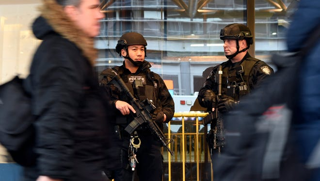 A pair of Port Authority police officers in tactical gear kept watch outside the Port Authority Bus Terminal on Tuesday. The terminal serves 260,000 commuters on a busy weekday, 92 percent of them from New Jersey.