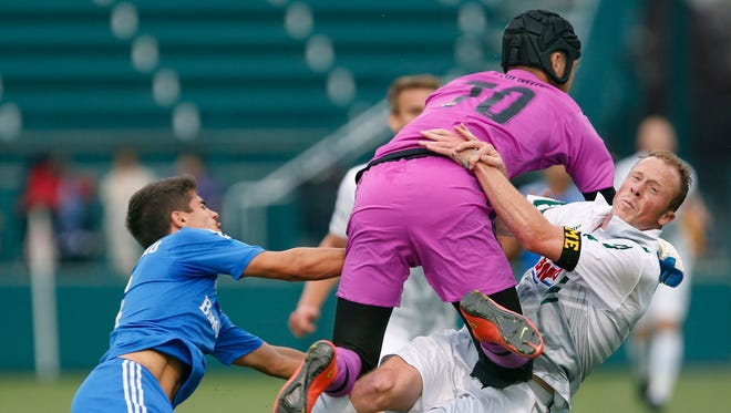Rochester Rhinos vs FC Montreal: Montreal's goalie David Paulmin jumps on top of Rhino's Timi Mulgrew who was attacking next to Montreal's Janouk Charbonneau in the first half at Sahlen's Stadium in Rochester.