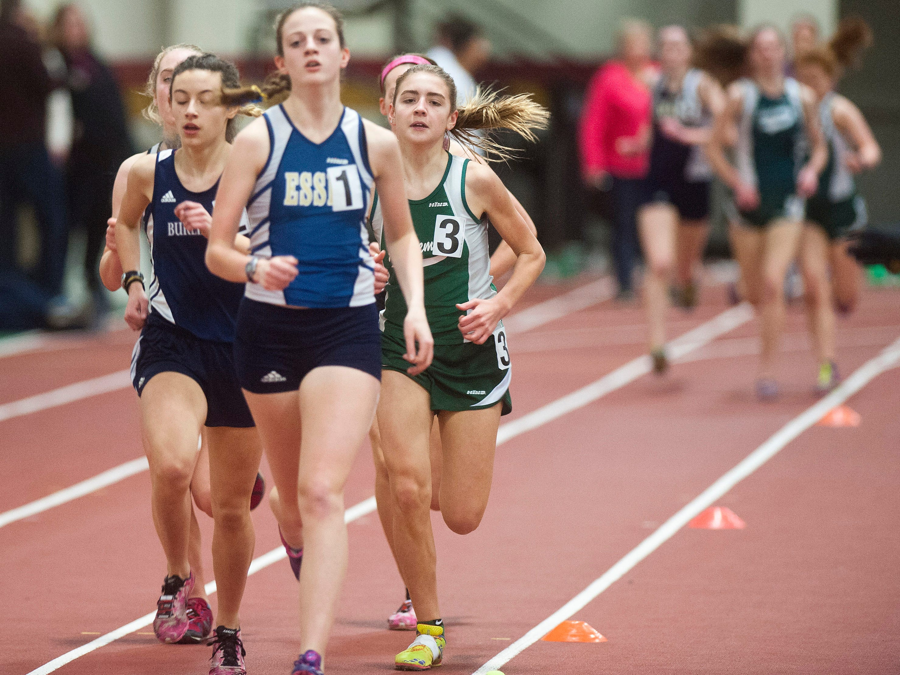 St. Johnsbury's Annie Cunningham (3) looks to overtake Essex's Rose Monahan during the Division I girls 1,600 meter race on Saturday at Norwich University.