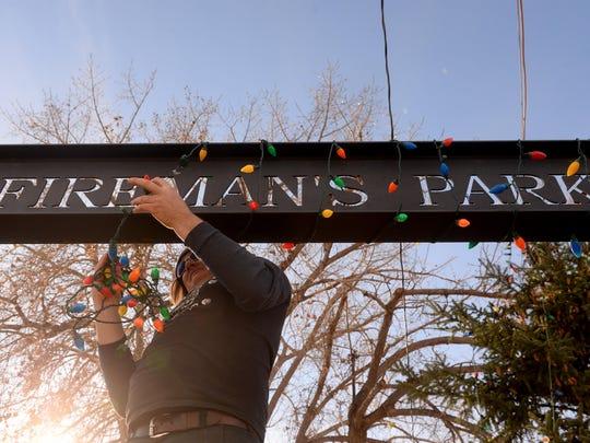Kyle Sorensen hangs Christmas lights in Fireman's Park