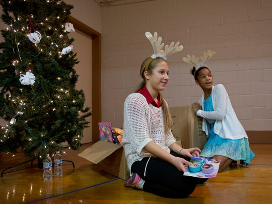 Sixth-grade students Mackenzie Rex and Hannah Sparling, both 12, handed out presents during a Winter Wonderland community event Thursday, Dec. 17, 2015 at East Shore Leadership Academy in Port Huron.