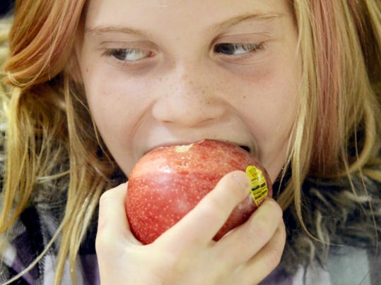 A girl bites into a free apple she received from a Family First Health representative during the 2012 apple giveaway in downtown York. This year's event will take place from noon to 1 p.m. Tuesday in Continental Square.