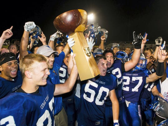 Cedar Crest's Evan Horn and Cedar Crest's Jake Kalbach hoist the Cedar Bowl after Cedar Crest defeated Lebanon 41-7 as they faced off in the 44th annual Cedar Bowl at Cedar Crest's Earl Boltz Stadium on Friday, September 4, 2015.