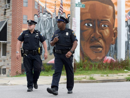 Baltimore police walk near a mural depicting Freddie
