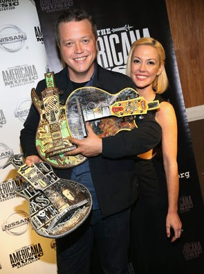 Jason Isbell and his wife Amanda Shires pose backstage with Isbell's armful of trophies at the annual Americana Music Association Honors and Awards Show at the Ryman Auditorium on Sept. 17 in Nashville, Tenn.