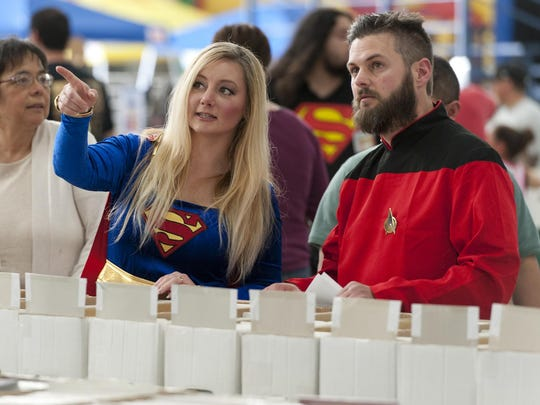 "Mo Montgomery (as Supergirl), left, and her husband Will Montgomery (looking much like Commander William T. Riker from ""Star Trek: The Next Generation"") browse comic books during the first Tulare Sci-Fi Con at the International Agri-Center in Tulare on Saturday, March 29, 2014."