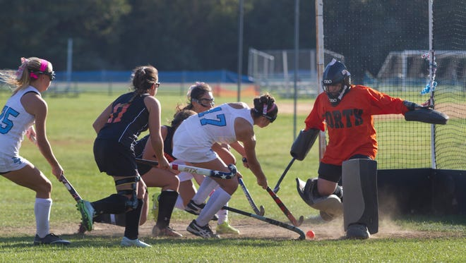 Middletown North goalie Emily Kernan kicks away a shot on goal by Freehold Township's Jess Pietracatelladuring first half action. Middletown North Field Hockey vs Freehold Township in SCT tourney action in Freehold Township on October 2015.