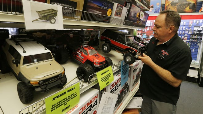 Bob Mazza, owner of Hobbytown, adjusts the display and looks over a remote control Bronco inside the store, Friday, July 6, 2018. The store has seen a decrease in sales and walk-in traffic since road construction began. Road construction should be completed in October or November.