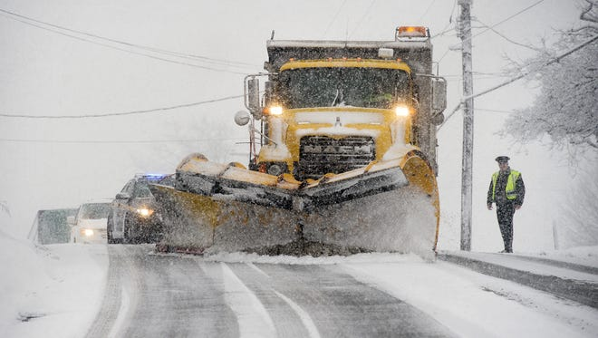 Police stop traffic so a snow plow can clear and salt a hill on North George Street in Manchester Township.