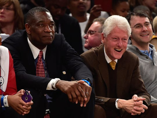 NBA legend Dikembe Mutombo and former U.S. president Bill Clinton take in the 2015 NBA All-Star Game from courtside.